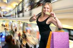 Shoppingpåsar och kreditkort för lycklig kvinna hållande Arkivbild