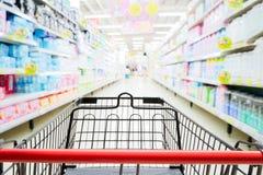 Shoppingspårvagn i supermarket med den blured supermarketgången och hyllabakgrund Arkivfoto