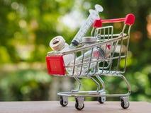 Shoppingspårvagn med injektionvisar- och medicinflaskor Hea arkivfoton