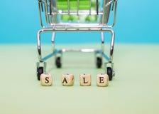Shoppingspårvagn och ordförsäljning från kuber på en grön bakgrund arkivbilder
