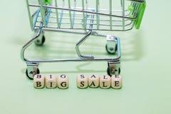Shoppingspårvagn och stor försäljning för ord från kuber på en grön backgro royaltyfri foto