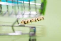 Shoppingspårvagn och stor försäljning för ord från kuber på en grön backgro royaltyfri bild