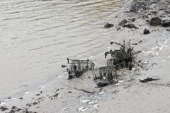 Shoppingspårvagnar och andra objekt som kastas in i ett Tidal River, täckas över av gyttja, slam och havsväxt som visar att skräp arkivbild