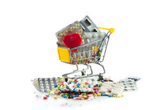 Shoppingspårvagn med preventivpillerar, hjärta som isoleras på vit bakgrund Arkivbilder