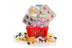 Shoppingspårvagn med preventivpillerar och medicin på vit Royaltyfria Foton