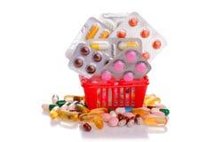 Shoppingspårvagn med preventivpillerar och medicin som isoleras på vit Royaltyfri Foto