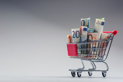 Shoppingspårvagn mycket av europengar - sedlar - valuta Det symboliska exemplet av att spendera pengar shoppar in, eller det förd Royaltyfri Bild