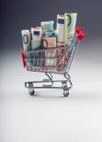 Shoppingspårvagn mycket av europengar - sedlar - valuta Det symboliska exemplet av att spendera pengar shoppar in, eller det förd Royaltyfri Foto