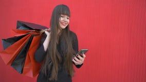 Shoppingtid, gör den unga lyckliga flickan köpet den online-användande smartphonen med pappers- påsar i händer på röd bakgrund stock video