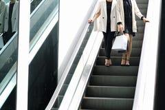 Shoppingvän, kvinnor som rymmer shoppingpåsar i shoppinggallerian arkivfoton