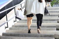 Shoppingvän, kvinnor som rymmer shoppingpåsar på gatan arkivbild