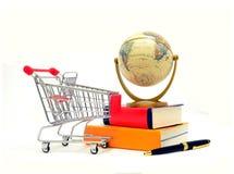 Shoppingvagn med böcker och jordklotet Arkivfoto