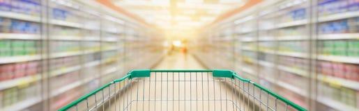 Shoppingvagn med bakgrund för supermarketgångsuddighet Royaltyfria Bilder