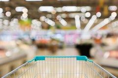 Shoppingvagn med defocused bakgrund för abstrakt supermarket Royaltyfria Bilder