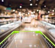 Shoppingvagn med den abstrakta supermarketlivsmedelsbutiken arkivfoto