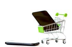 Shoppingvagn med den mobil telefonen på en isolerad bakgrund Smartph royaltyfri fotografi