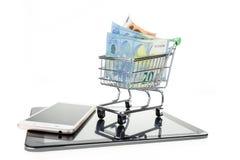 Shoppingvagn med euro på minnestavlan och smartphonen Royaltyfri Fotografi