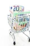 Shoppingvagn med euro som isoleras på vit Arkivfoton