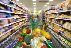 Shoppingvagn med foods i supermarket Arkivfoton