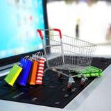 Shoppingvagn med kartonger på bärbara datorn. 3d Royaltyfri Foto
