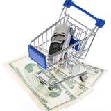 Shoppingvagn med leksakbil- och pengardollar Royaltyfri Bild