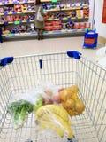Shoppingvagn med livsmedelsbutiken på supermarket Royaltyfri Foto