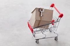 Shoppingvagn med modellen av papphuset på grå bakgrund, köpande ett nytt hem eller försäljning av fastighetbegreppet royaltyfri foto