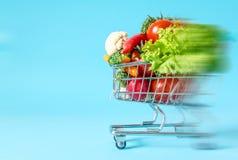 Shoppingvagn med närbild för nya grönsaker på blå bakgrund royaltyfri bild