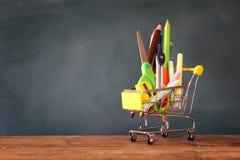 Shoppingvagn med skolatillförsel framme av svart tavla royaltyfri fotografi