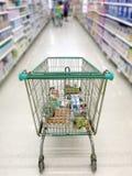 Shoppingvagn med supermarketgången och hyllor i suddighetsbakgrund Arkivfoton