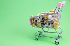 Shoppingvagn mycket av drog- och medicinpiller farmaceutiskt kostat begrepp läkarbehandlingar i vagnen Köpandemediciner arkivbilder