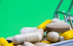 Shoppingvagn mycket av drog- och medicinpiller farmaceutiskt kostat begrepp läkarbehandlingar i vagnen Köpandemediciner Slutet be royaltyfri foto