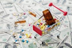 Shoppingvagn mycket av drog- och medicinpreventivpillerar på dollarpengarbakgrund arkivfoton