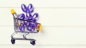 Shoppingvagn mycket av easter chokladägg Lyckligt påskkort med kopieringsutrymme Påskförsäljningar Festliga ägg som slås in i fol royaltyfri fotografi