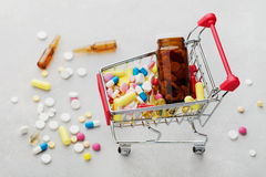 Shoppingvagn mycket av farmaceutiska drog- och medicinpreventivpillerar Arkivbild