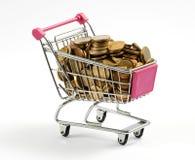 Shoppingvagn mycket av guld- mynt Arkivfoton