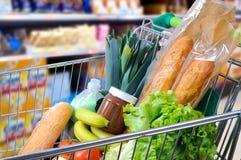 Shoppingvagn mycket av mat i supermarketsidosikten arkivbild