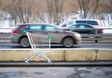 Shoppingvagn och bilar arkivbilder
