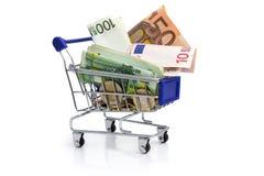 Shoppingvagn och pengar Arkivfoto