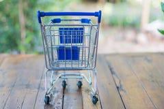 Shoppingvagn på den wood tabellen Arkivbilder