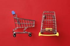 Shoppingvagn på en röd bakgrund royaltyfri fotografi
