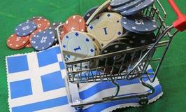 Shoppingvagnen av kasinot gå i flisor mycket över flaggan av Grekland Arkivfoto