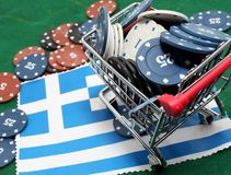 Shoppingvagnen av kasinot gå i flisor mycket över flaggan av Grekland Arkivbild