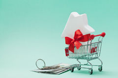 Shoppingvagnen med huset dekorerade pilbågebandet, dollar pengar och gruppen av tangenter Köpande ny hem-, gåva- eller försäljnin royaltyfri foto