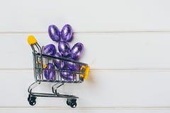 Shoppingvagnen mycket av violetta easter ägg, på vit backgdrop, kopierar utrymme Arkivbild