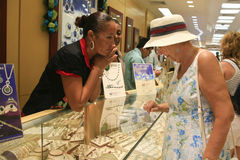 Shoppping in Jewelery Store, Oranjestad, Aruba. A senior woman shops for a ring in a jewelery store in Oranjestad, capital of Aruba. Two sales ladies are looking Royalty Free Stock Photography