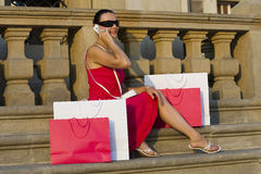 After The Shops. A classically beautiful Mediterranean woman sitting in the square of a European city surrounded by full shopping bags and chatting on her mobile Royalty Free Stock Photos