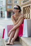 After The Shops. A classically beautiful Mediterranean woman sitting and thinking surrounded by full shopping bags Stock Images