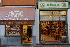 Shops with chocolate and beer traditional in Belgium. BRUSSELS, BELGIUM - OCTOBER 15, 2015: Street photography with two shops in Bruxelles which represent the royalty free stock image