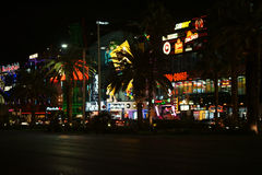 Shops on the Las Vegas Boulevard. Las Vegas, USA - December 23, 2015: Traffic on Las Vegas Boulevard with a collection of flashy lighted stores and shops behind Royalty Free Stock Photos